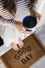 Low section of woman holding coffee while standing on doormat
