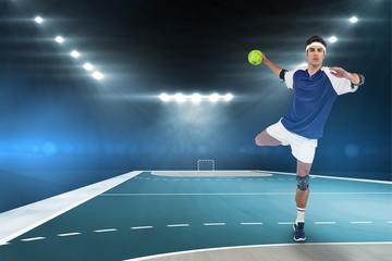 Portrait of sportsman throwing a ball against handball field indoor