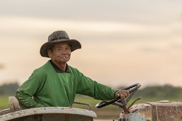a senior male farmer smoking and sitting in a tractor during sun