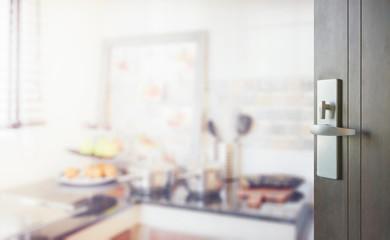 opened wooden door to blurred modern kitchen interior as background