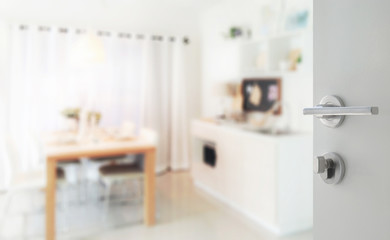opened white door to modern kitchen with wooden dining table next to pantry