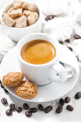 cup of espresso and sweet cookies on a white table, vertical