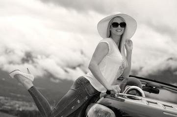 Junge blonde Frau mit Sonnenbrille, Hut und Cabrio