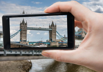 Tourist is photographing London Bridge with smartphone.