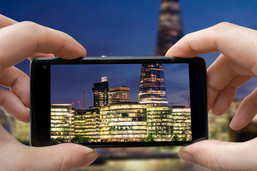 Tourist is taking photo of London in night with smartphone.