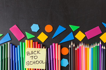 "Back to school background with a lot of colorful felt-tip pens and colorful pencils in row and  title ""Back to school"" written on the yellow piece of paper on the black school chalkboard"