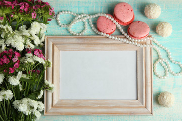 a bouquet of chrysanthemum with wooden frame for photo on wooden background with macaroon and beads