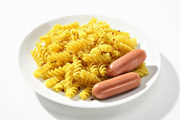 Expertly cooked fusilli with spice served with an accompanying sausages on white ceramic plate. Close up, high resolution product.