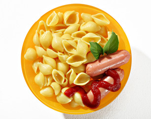 Expertly cooked macaroni shells with sausages in orange plate on white background. Close up, top view, high resolution product.