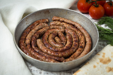 fried sausages on a frying pan on a wooden background. selective