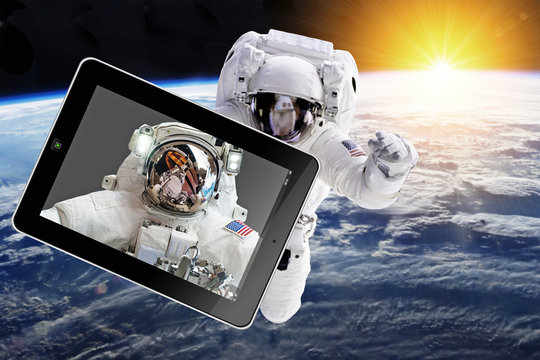 Astronaut with tablet in space - Elements of this image furnished by NASA