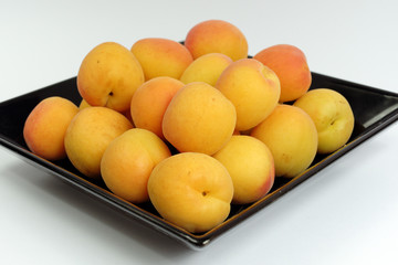 Ripe apricots on a black plate