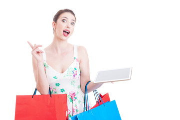 Pretty lady holding shopping bags and tablet having an idea
