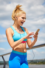 Sporty woman on pier over river holding phone