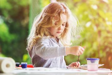 Portrait of little blonde girl painting, summer outdoor.