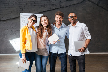 Multiethnic group of happy young business people standing in office