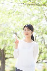 指差しをする女性、新緑