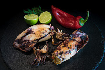 Fried squids, stuffed with rice on black dish