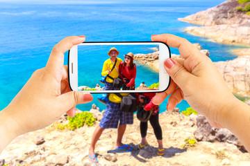 Smartphone photographing Asian lover couple at Similan Island, Koh Ta Chai, Andaman Sea, Thailand