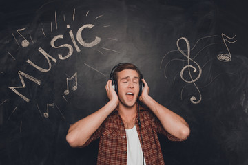 Handsome young man in head-phones listening music and singing