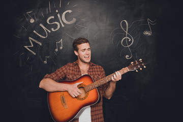 Handsome young instrumentalist playing on the guitar and singer