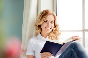 Portrait of beautiful smiling relaxed woman reading book