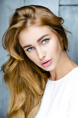 Portrait of young beautiful woman. Long, light, wavy hair and makeup