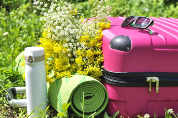 Suitcase with thermos and yoga mat