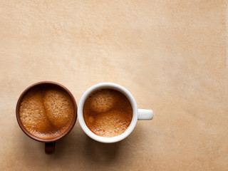 Two coffee espesso cups on brown table. Top view copy space