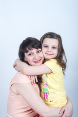 the daughter and mother together in each other's arms on a white background