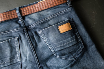 Back pocket of blue jeans with leather belt