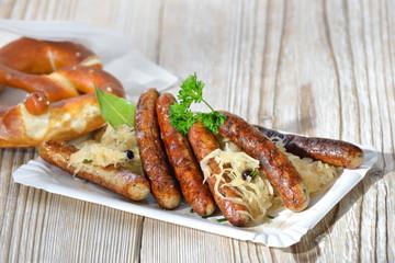 Sechs auf Kraut - Sechs deftige Nürnberger Rostbratwürste auf Sauerkraut mit einer Breze serviert - Six fried Bavarian sausages from Nuremberg served with sauerkraut and a pretzel