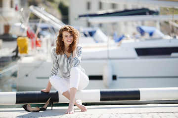 Stylish young woman with gray eyes,curly red hair and sweet smile,dressed in white pants and a bright striped shirt,posing on the pier next to the yacht club and the sea, yachts and boats