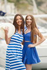 Two beautiful women,brunette with long straight hair,cute smile,in the hands of one of the bridesmaids-a large white straw hat,pasirayi in the Harbor on the background of boats and yachts