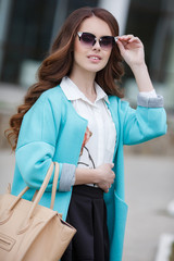 Young beautiful brunette woman with long curly hair,wears dark sun glasses,dressed in a blue cloak,white shirt and black skirt, holding a leather bag beige posing outdoors in the city in the spring