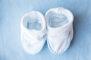 close up of baby bootees for newborn boy on blue