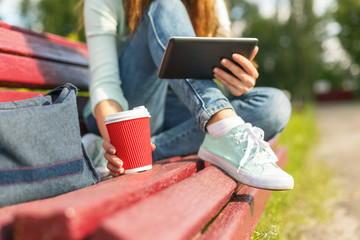 Young woman with a coffee to go and tablet pc on a bench