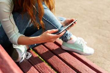 Young woman with a coffe to go and tablet pc on a bench