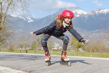preteen girl on roller skates in helmet at track