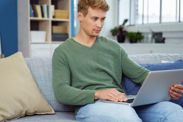 mann mit laptop auf dem sofa zu hause