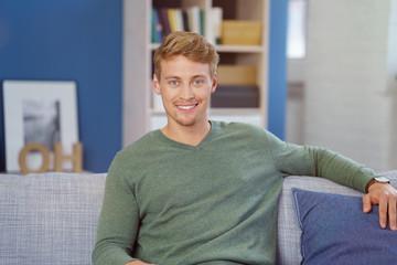 lächelnder mann sitzt auf dem sofa zu hause