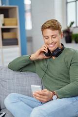 lächelnder mann hört musik mit seinem handy
