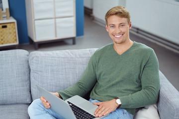 mann sitzt entspannt auf dem sofa mit notebook