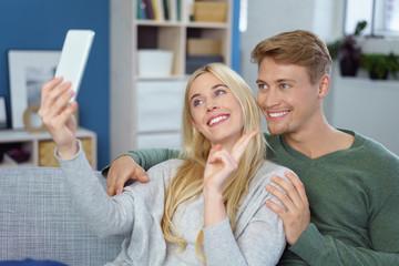 lachendes paar macht ein selfie zu hause