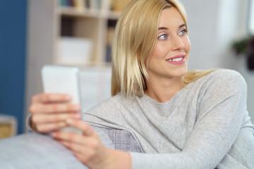 schöne blonde frau mit mobiltelefon auf dem sofa