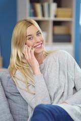 lächelnde junge frau telefoniert zuhause mit ihrem handy