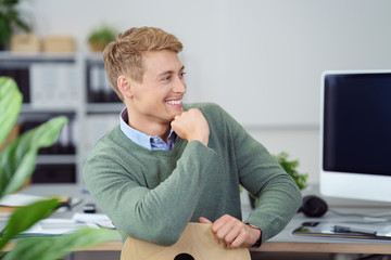 lachender mann am schreibtisch im büro