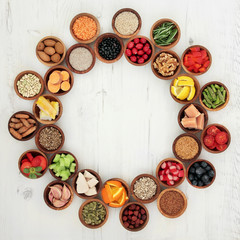 Healthy Super Food Selection.  Food selection in wooden bowls forming a wheel over distressed white wood background. High in antioxidants, vitamins, minerals and anthocyanins.