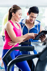 Coach evaluating performance of woman on treadmill