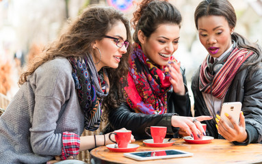 Women in cafe showing pictures on smart phone